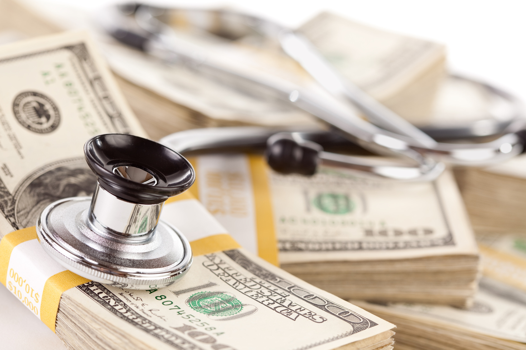 Stethoscope Laying on Stacks of Hundred Dollar Bills with Narrow Depth of Field.